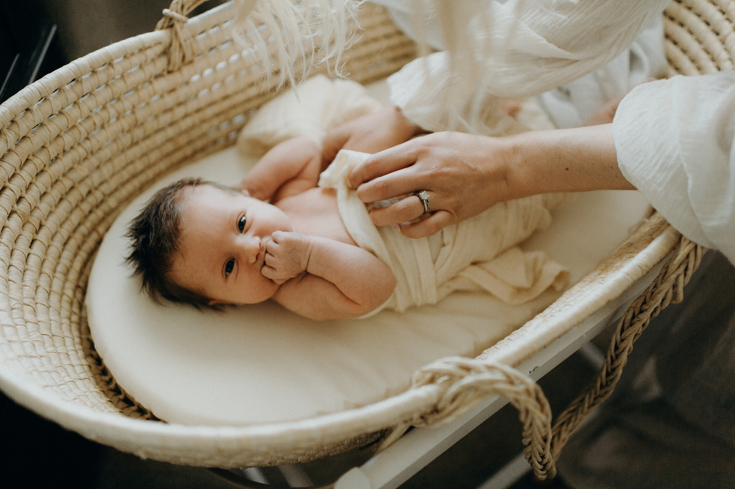 newborn baby in basket with mother nearby