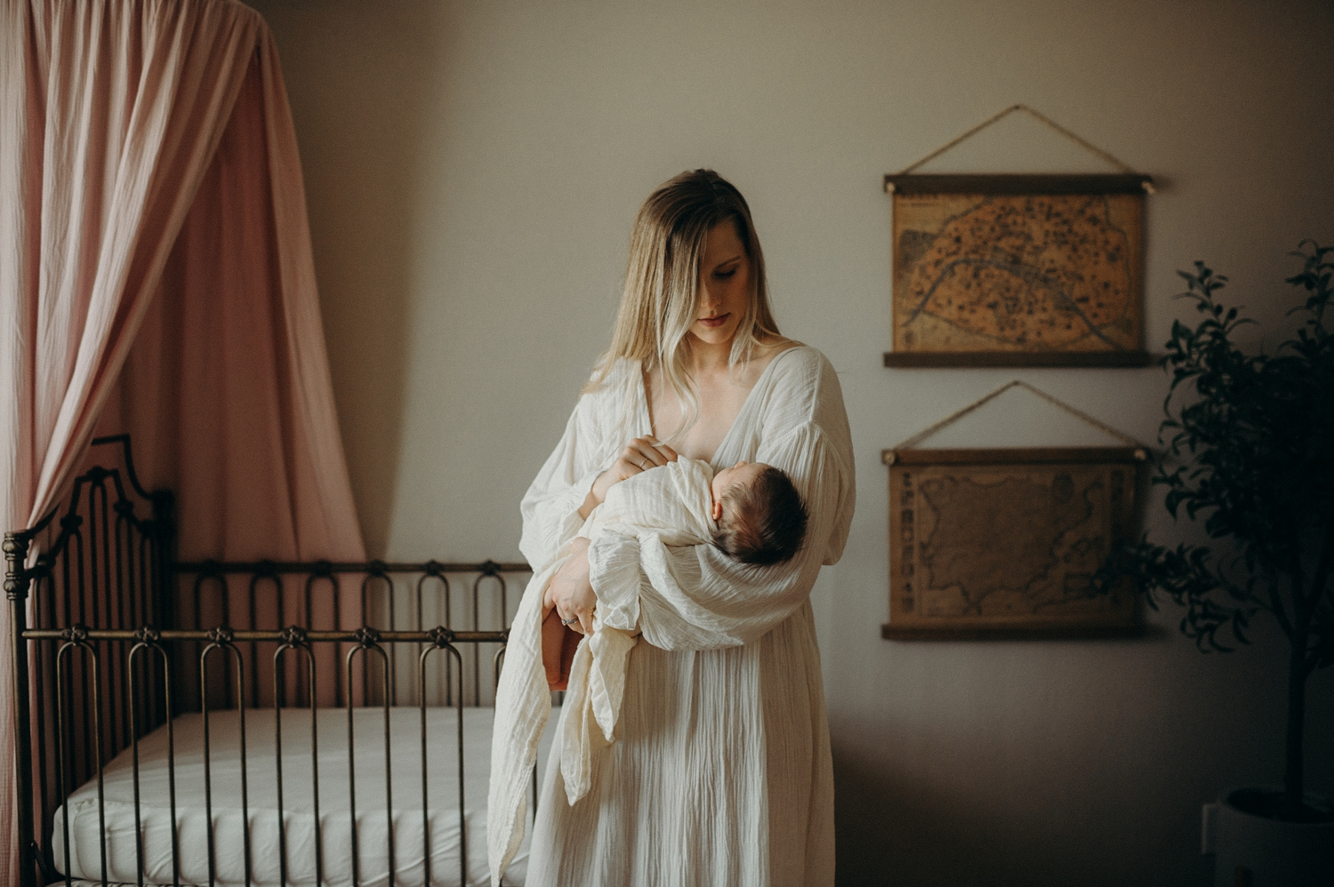 mother holding baby next to crib in nursery