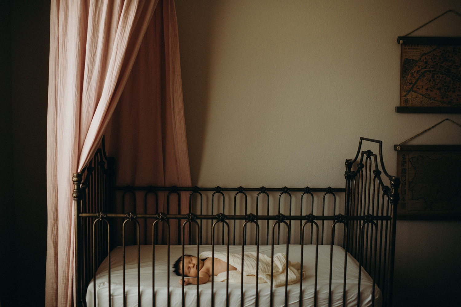 baby in crib with pink canopy above