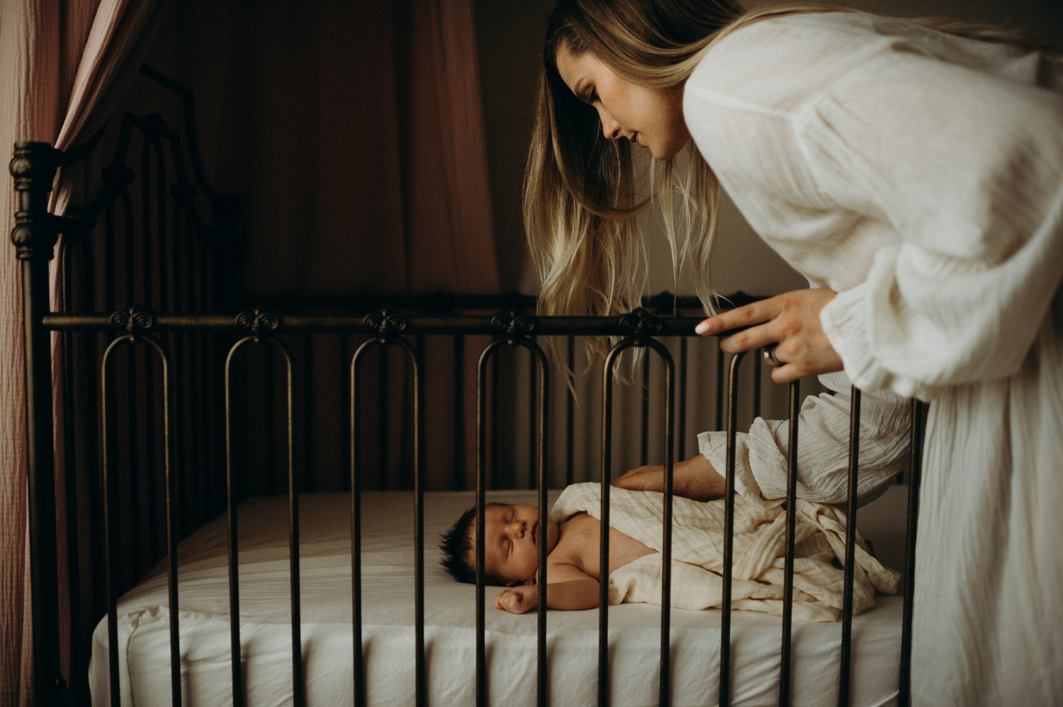 mother checking on baby in crib at home